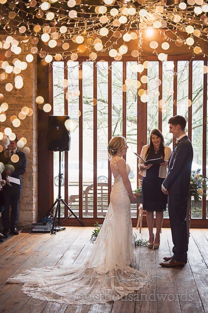 Bride and groom make wedding vows under fairy lights Dorset barn wedding venue
