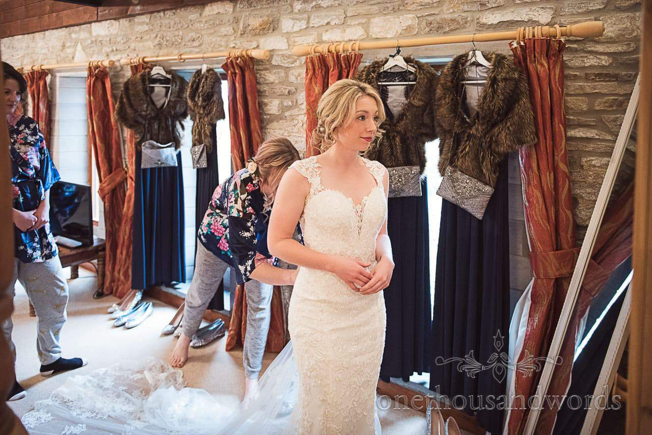 Bride looks in mirror as bridesmaids button up her dress in stone barn room