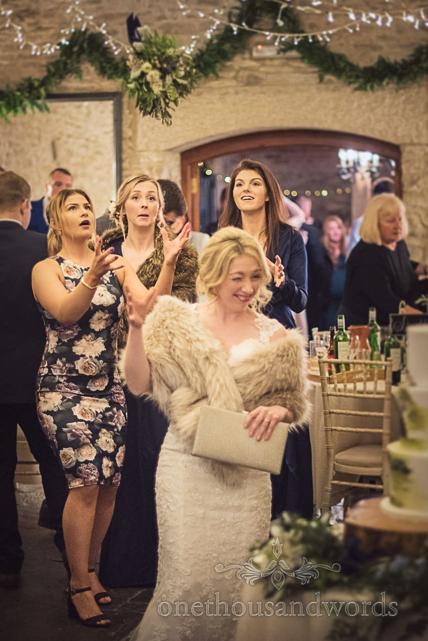 Bride throws wedding bouquet over her shoulder at Kingston Country Courtyard