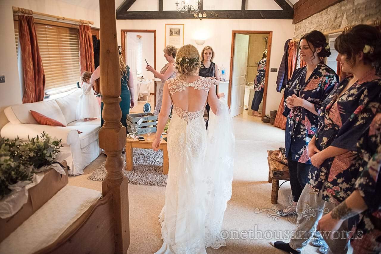 Bride walks in wedding dress first time wedding morning watched by bridesmaids