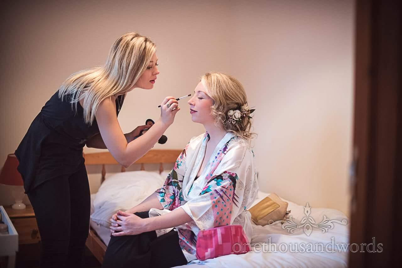 Bride has wedding makeup applied by makeup artist on wedding morning in Dorset