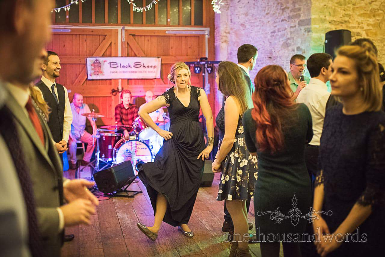 Bridesmaid in navy blue funny dance at wedding barn dance in Dorset
