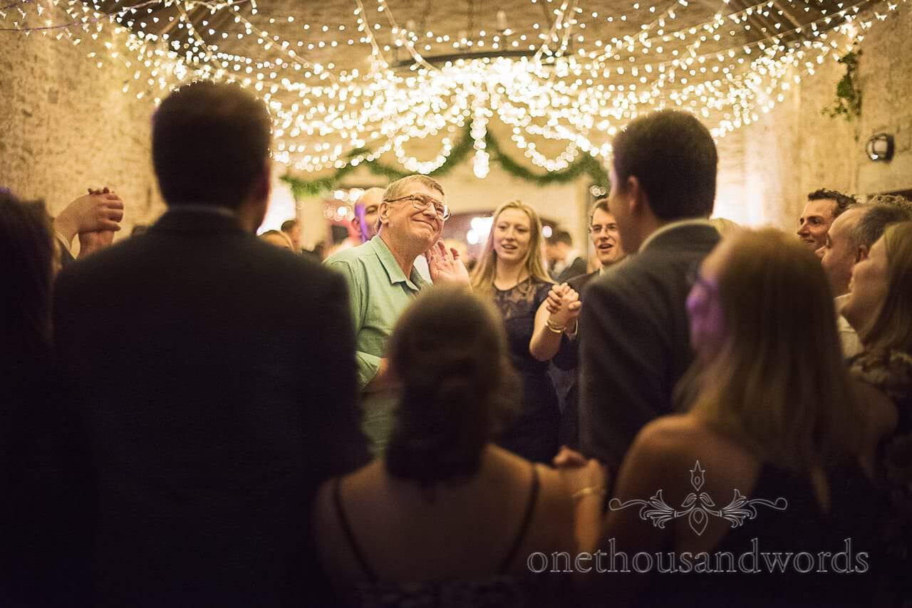 Ceilidh band caller listens to wedding guests enjoying a barn dance