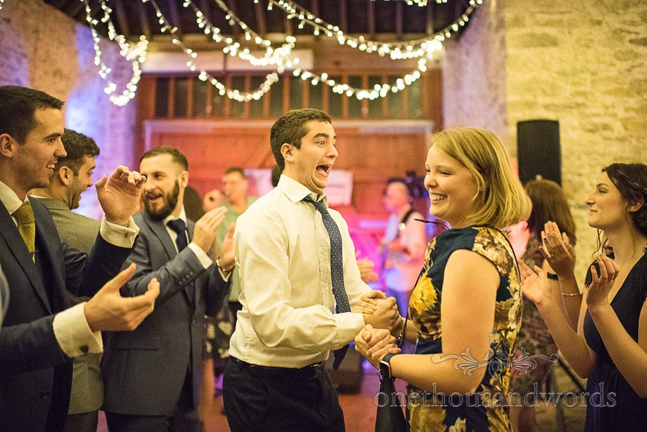 Ceilidh dancing wedding guests with funny faces at Dorset barn wedding venue