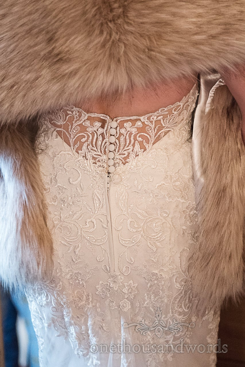 Close up photograph of lace detailing buttons on back of brides white wedding dress