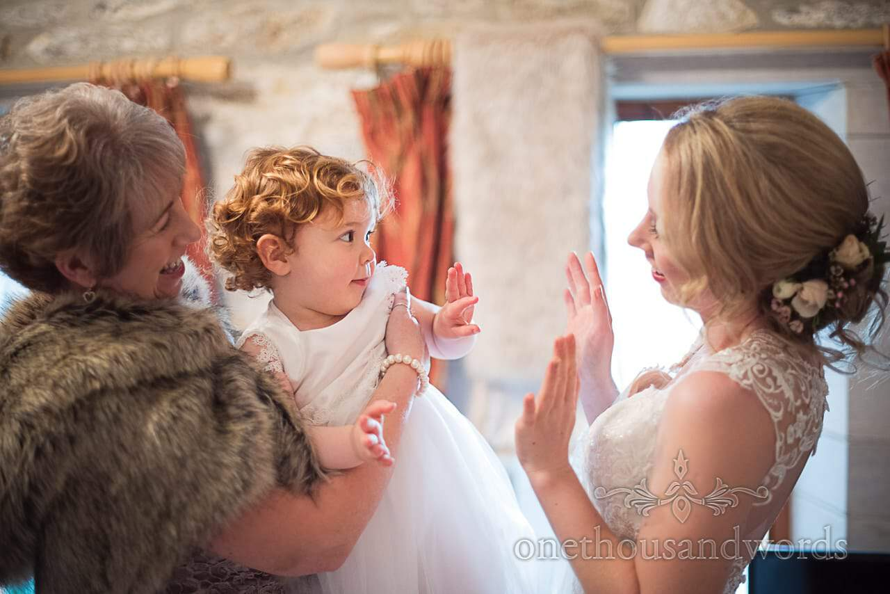 Cute flower girl dances with bride and mother on wedding morning at Dorset barn