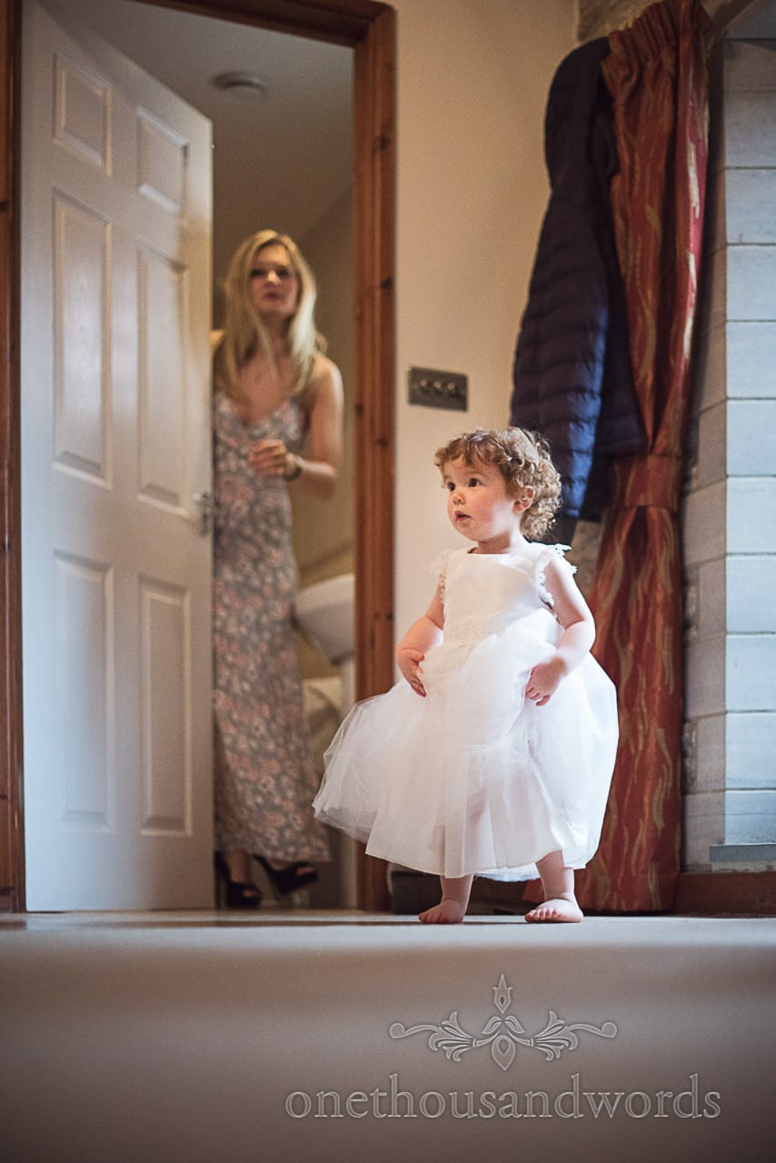 Cute flower girl in white dress without shoes on wedding morning in Dorset barn