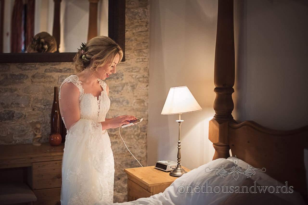 Documentary wedding photograph of bride in white wedding dress checking phone