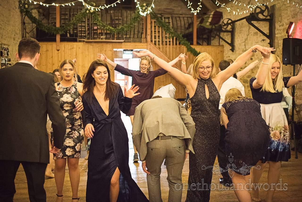 Documentary wedding photograph of ceilidh dancing at Dorset barn wedding venue