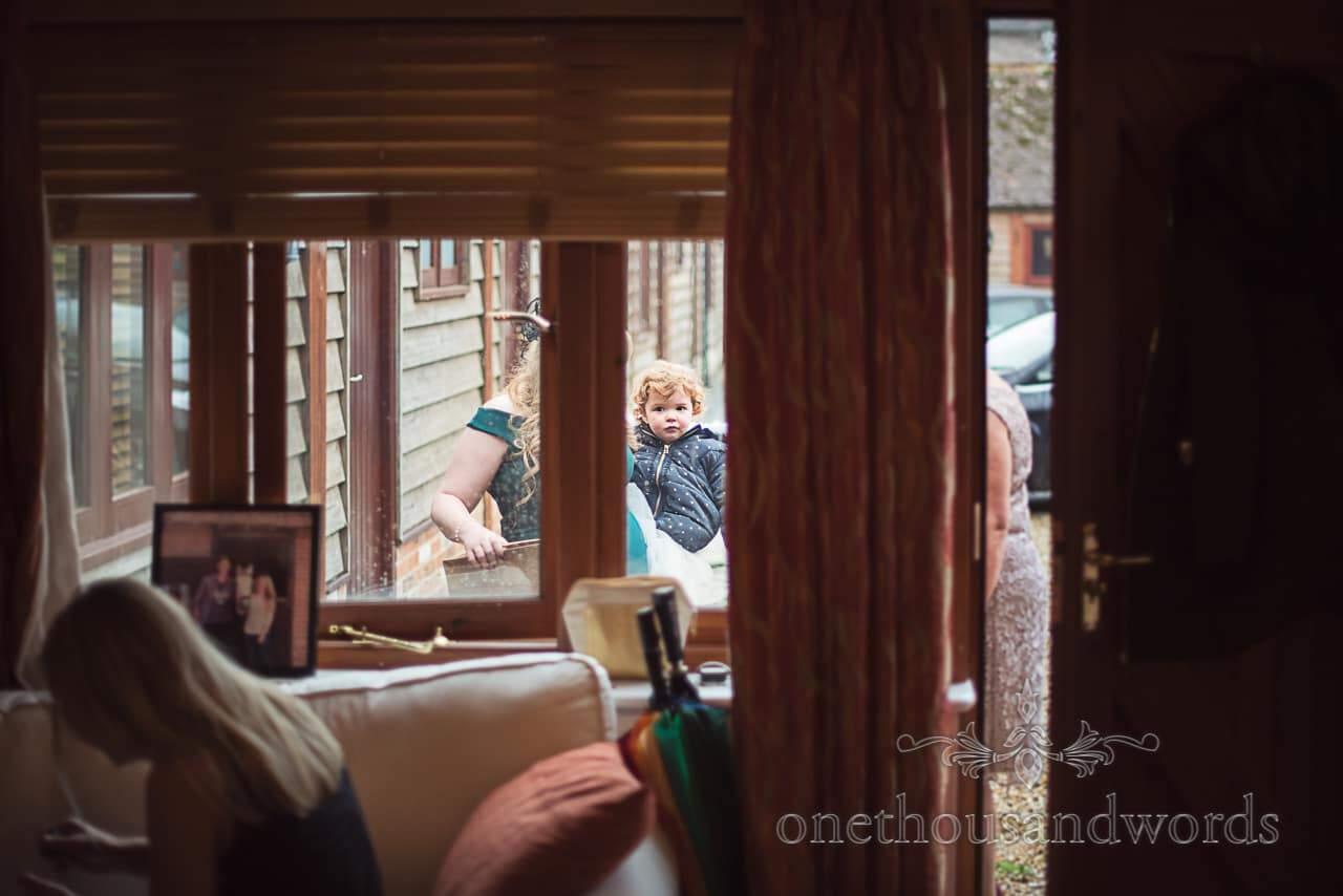 Documentary wedding photograph cute child flower girl arriving at Dorset wedding venue