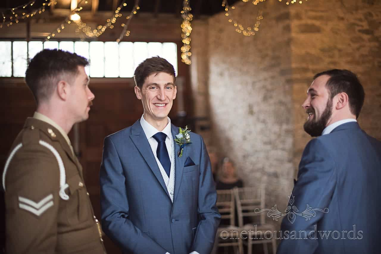 Documentary wedding photograph of groom in blue suit waiting for bride