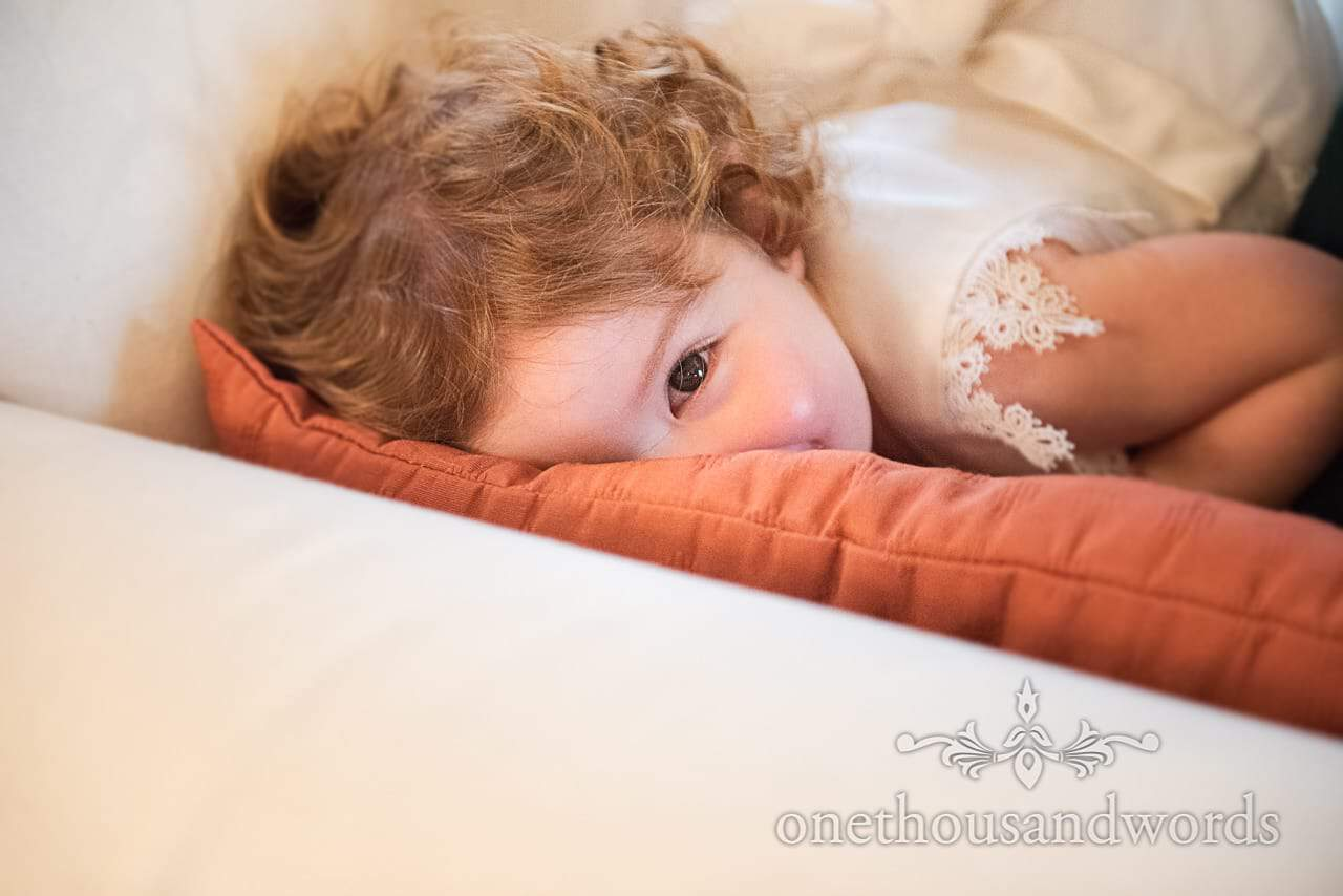 Flower girl plays peek a boo with wedding photographer during bridal preparations