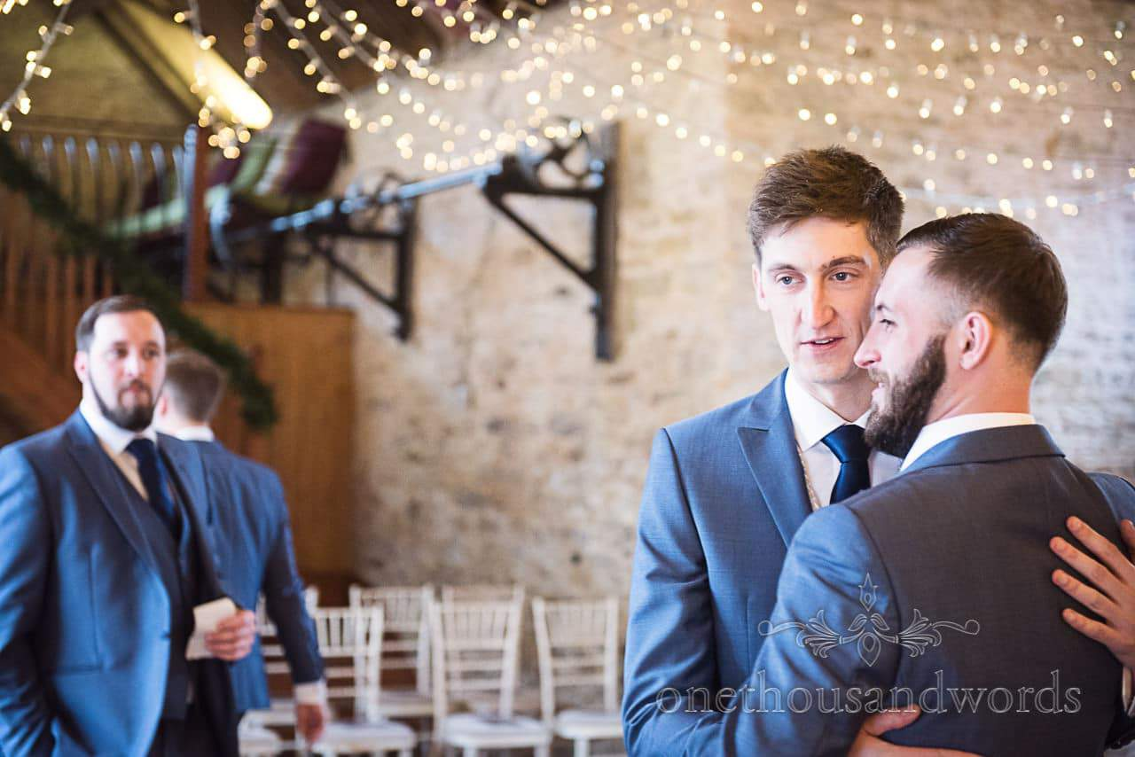 Groom and best man hug on wedding morning whilst waiting for wedding guests