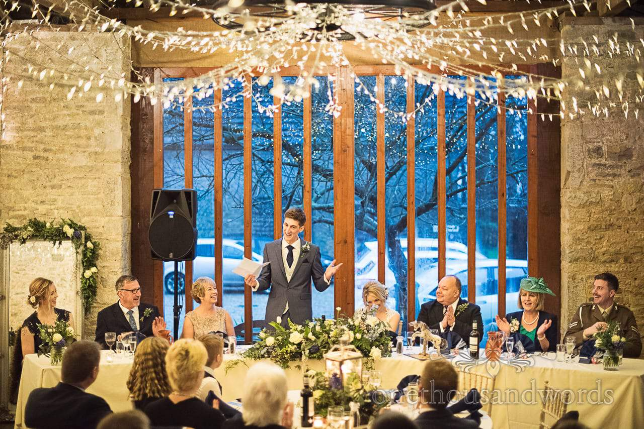 Groom delivers wedding speech at top table under fairy lights at Dorset barn venue