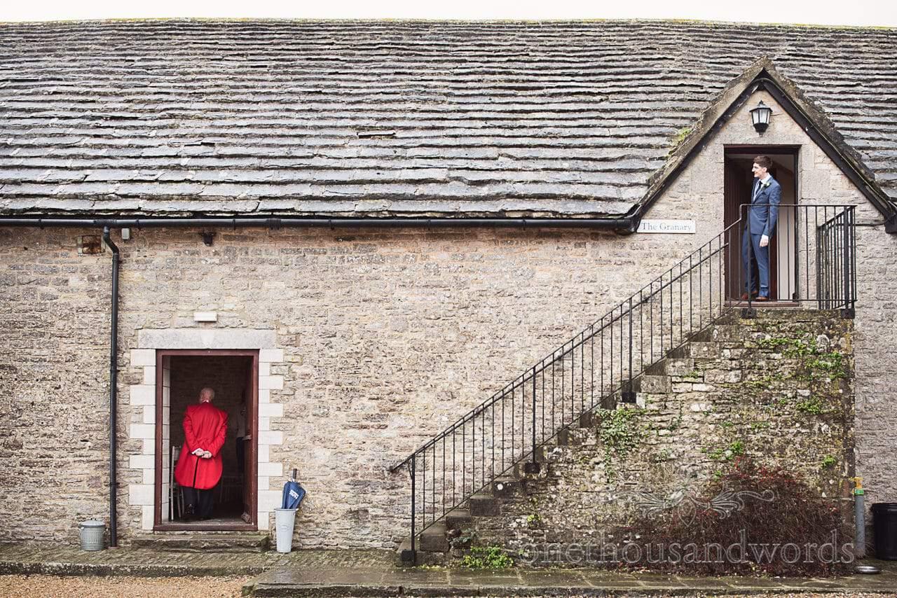Groom looks out of Kingston Country Courtyard door as MC in red suit looks in door