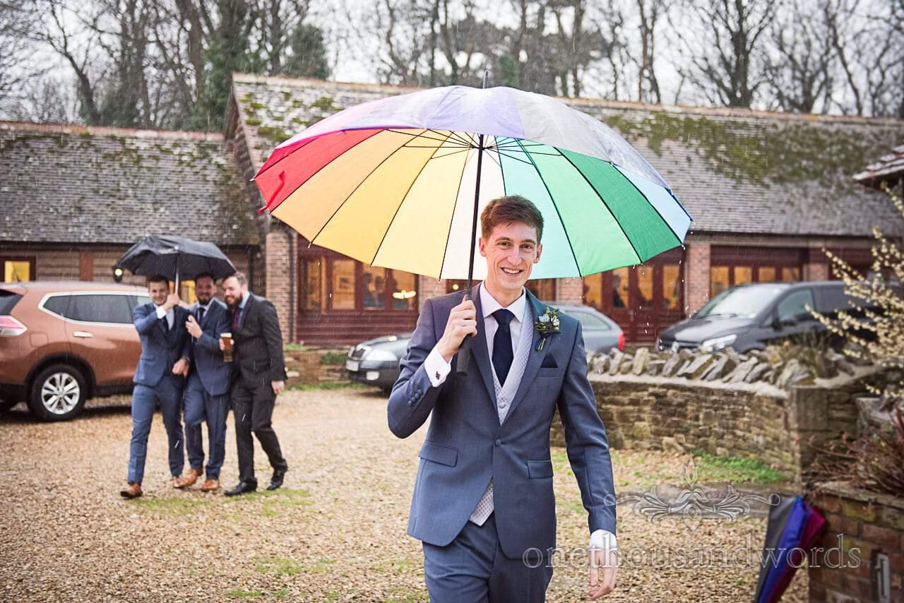 Groom under umbrella followed by groomsmen in rain at Kingston Country Courtyard