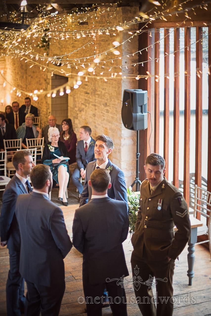 Groom waits for bride under fairy lights at Dorset barn wedding venue