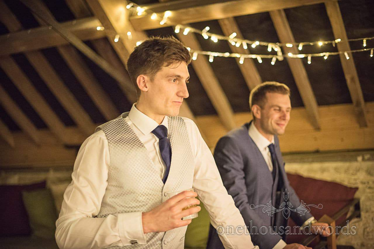 Groom in wedding barn with fairy lights watches wedding guests dancing