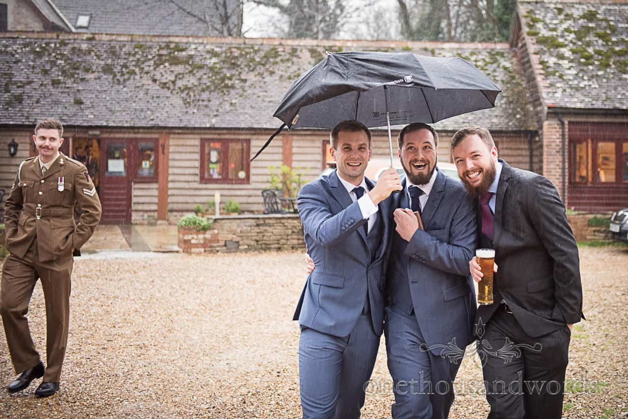 Groomsmen shelter from rain under umbrella at Kingston Country Courtyard venue