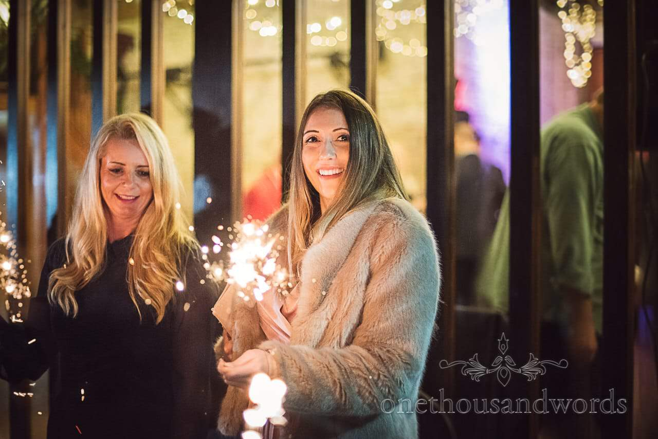 Happy winter wedding guests with sparklers outside barn wedding venue in Dorset