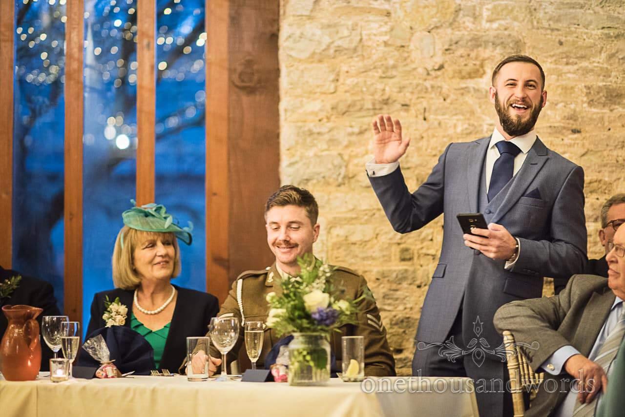 Laughing best man give wedding speech at Dorset Courtyard wedding barn