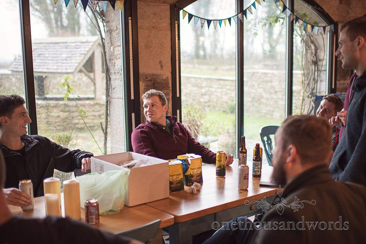 Laughing groomsmen drink cans and bottles of cider and beer on wedding morning