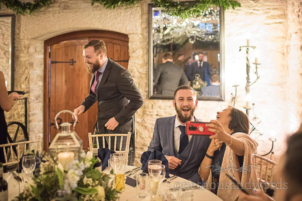Laughing wedding guests take selfies at Kingston Country Courtyard reception