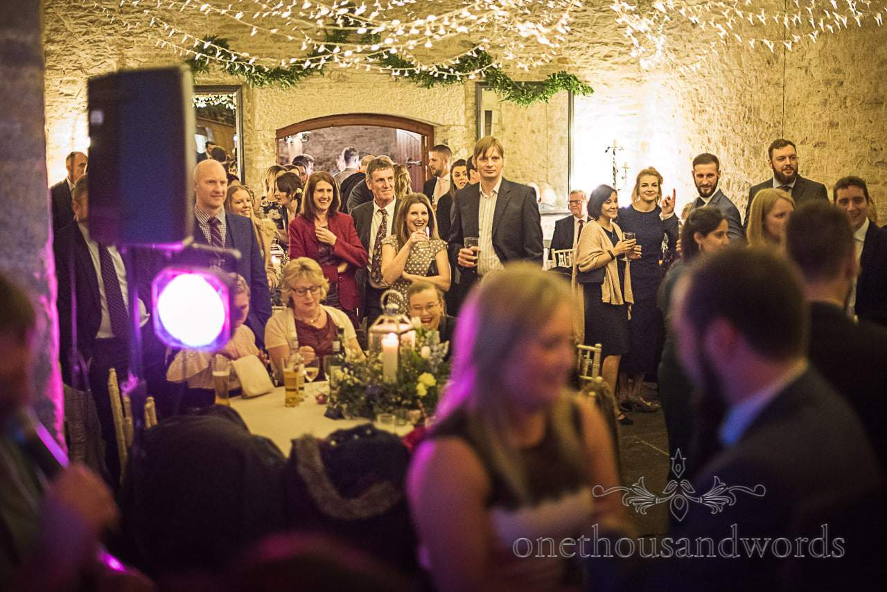 Laughing wedding guests watch ceilidh band at Dorset barn wedding venue