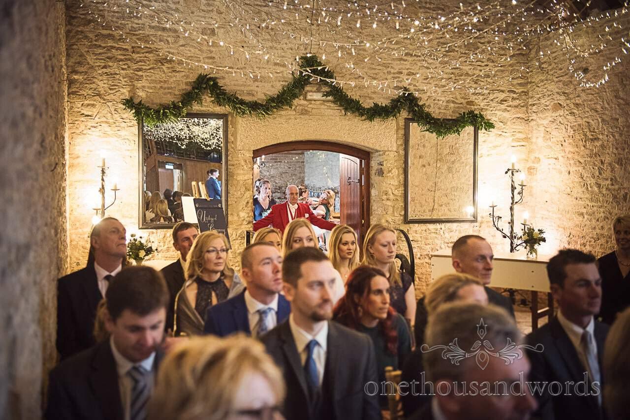 Master of ceremonies in red suit opens barn doors for wedding ceremony in Dorset