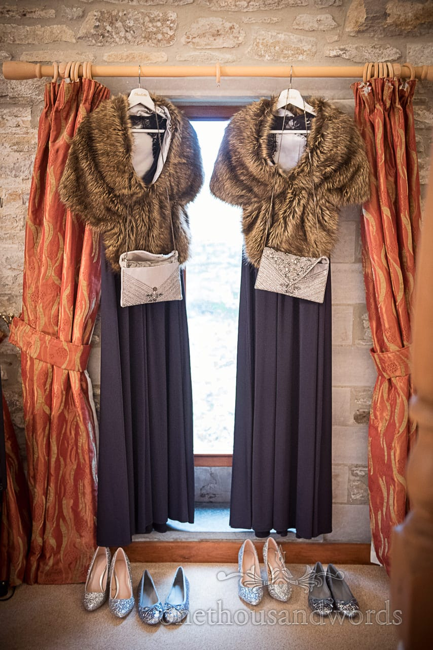 Navy blue bridesmaids dresses with brown faux fur stoles hang in stone barn window