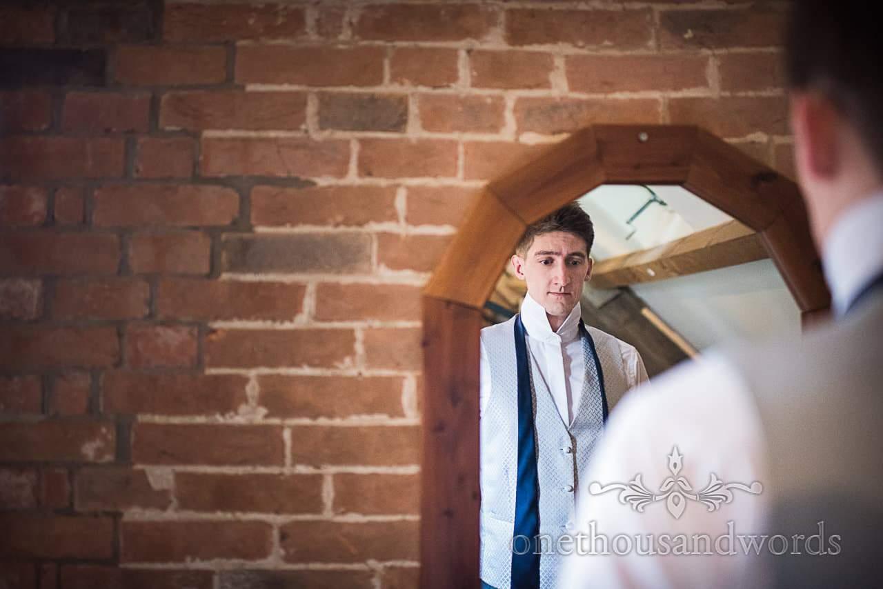 Nervous groom looks at blue wedding tie in mirror on wedding morning