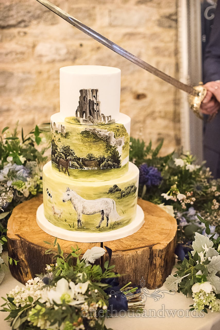 Wedding cake with Dorset countryside castle and horse painting cut with sword