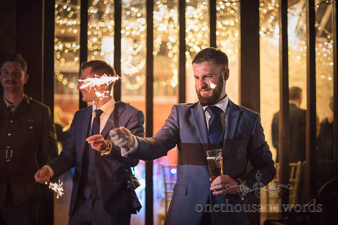 Wedding guest concentrates on wedding sparklers at Kingston Country Courtyard