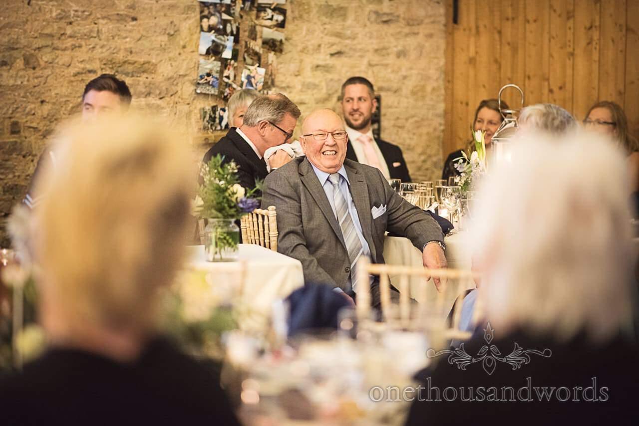Wedding guest laughs at speeches in Dorset barn wedding venue