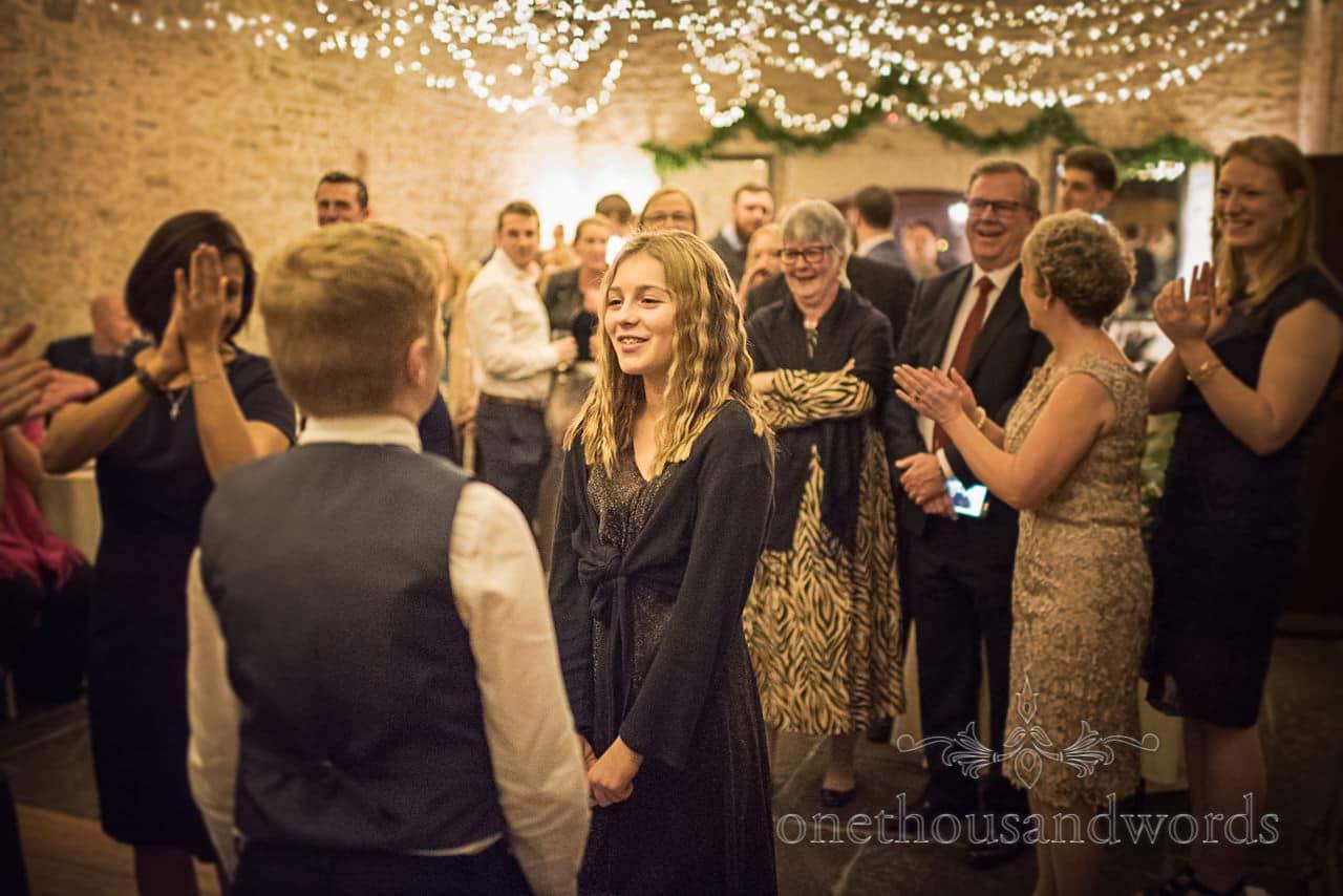 Wedding guests applaud children joining in Dorset wedding barn dance