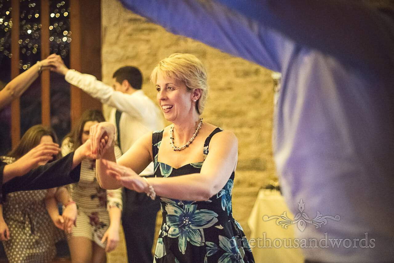 Wedding guests ceilidh dancing at Kingston Country Courtyard, Dorset