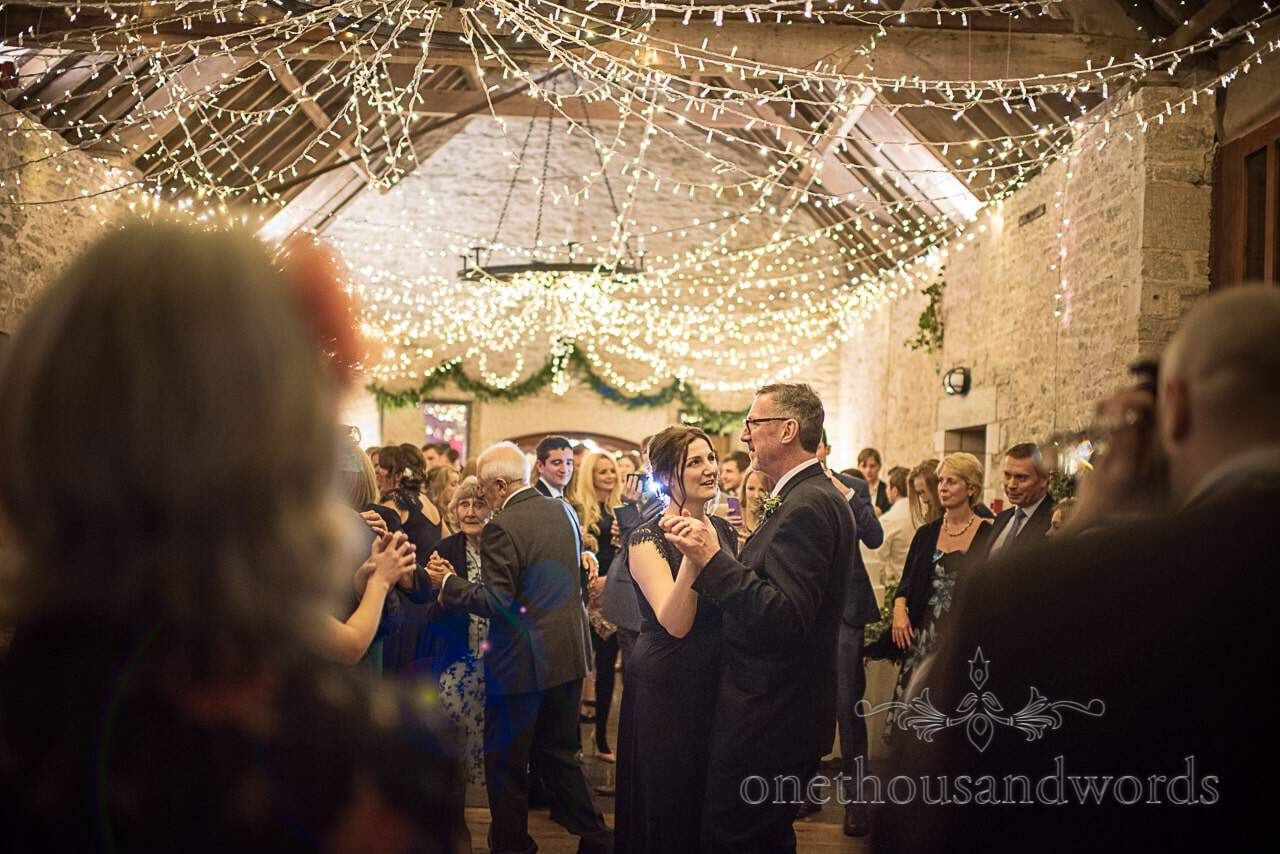 Wedding guests dancing under fairy lights at Kingston Country Courtyard venue