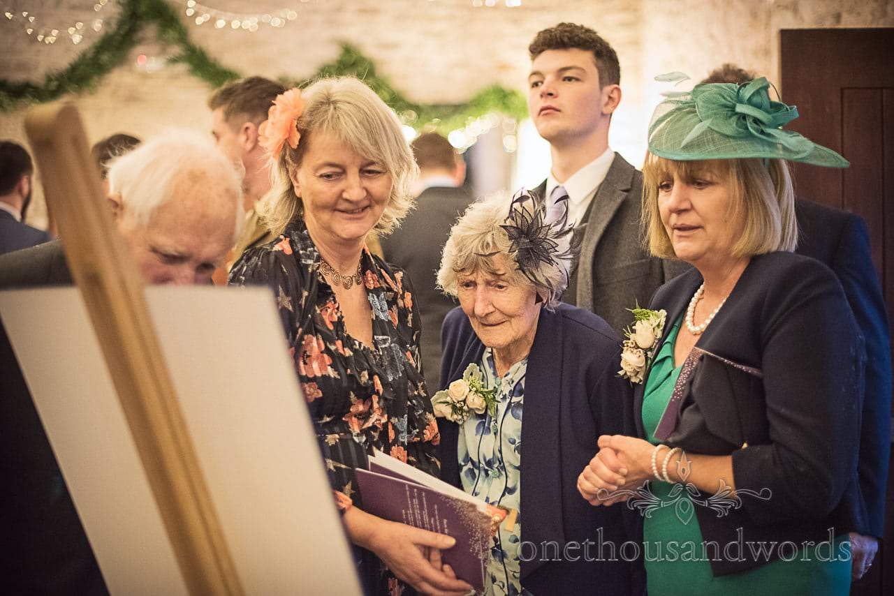 Wedding guests examine table plan at Kingston Country Courtyard wedding venue
