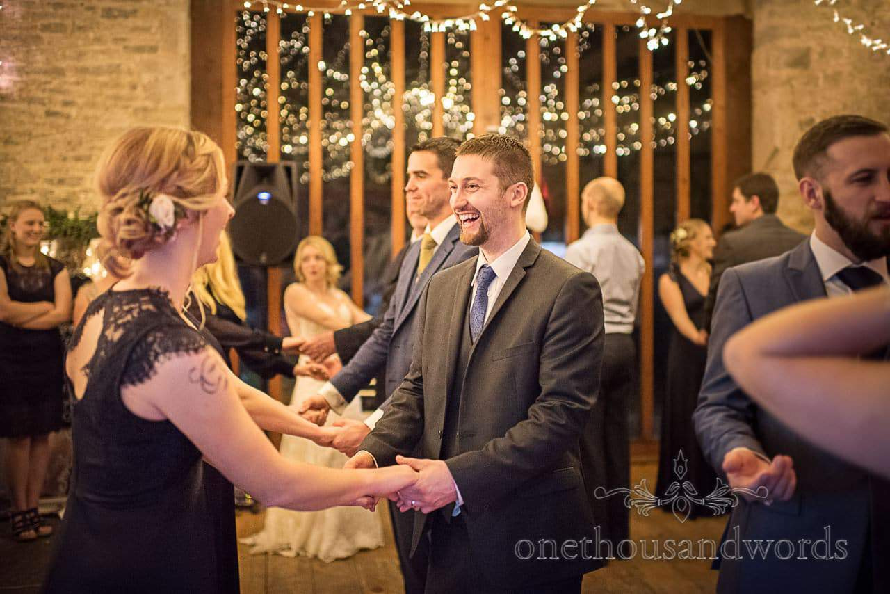 Wedding guests hold hands in barn dance at Kingston Country Courtyard wedding