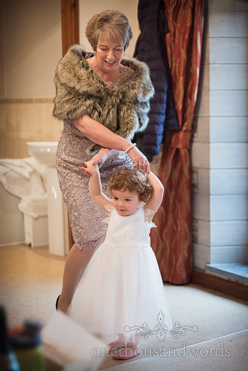 wedding morning photo cute flower girl white dress dances with mother of the bride