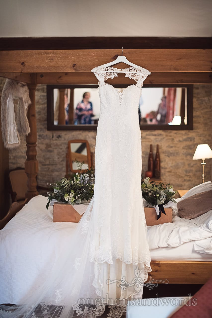 White detailed wedding dress hangs above bed at Kingston Country Courtyard