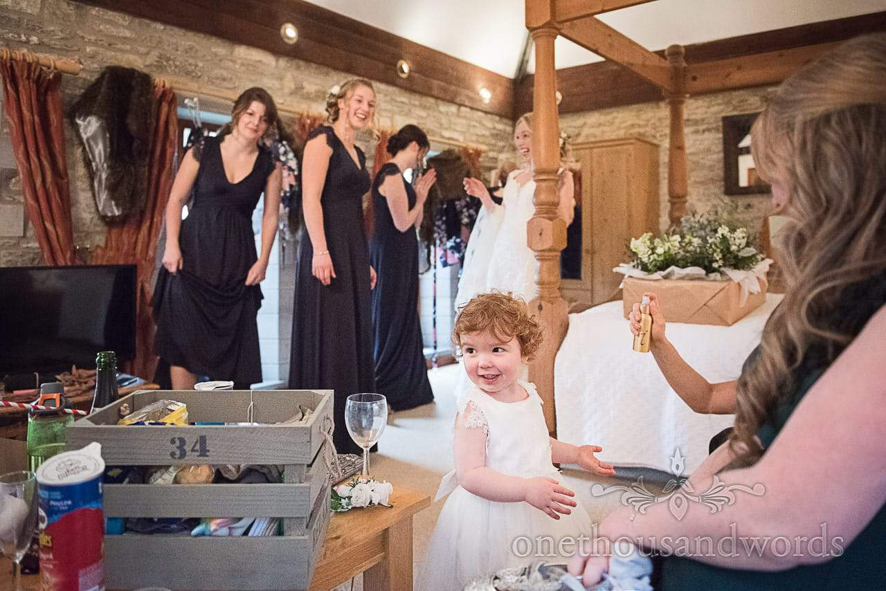 Young flower girl has makeup fixing spray watched by bridesmaids wedding morning