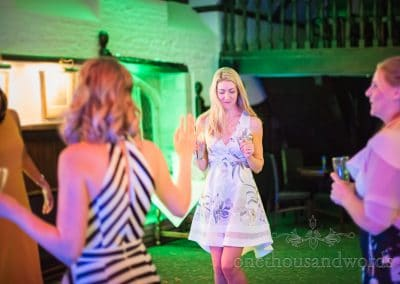 Beautiful blonde wedding guest in floral print dress dances under green disco lighting
