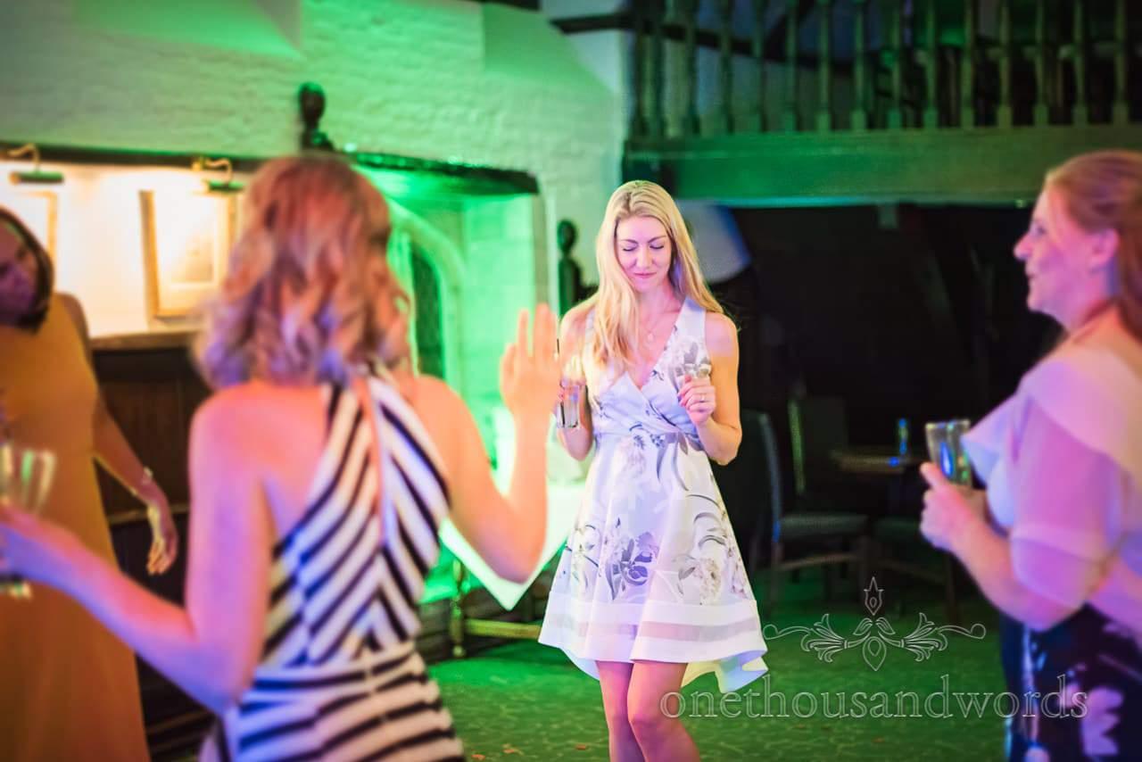 Beautiful blonde wedding guest in floral print dress dances under green disco lighting