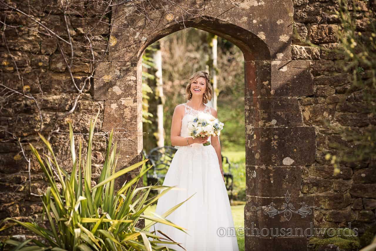 Beautiful blonde bride in stone doorway at Athelhampton House