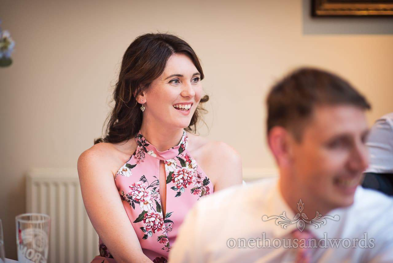 Beautiful wedding guest in pink floral dress laughs at wedding speeches