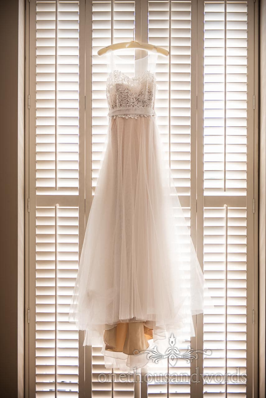 Beautiful backlit White Wedding Dress with lace detailing Hangs in wooden Slatted Window on wedding morning