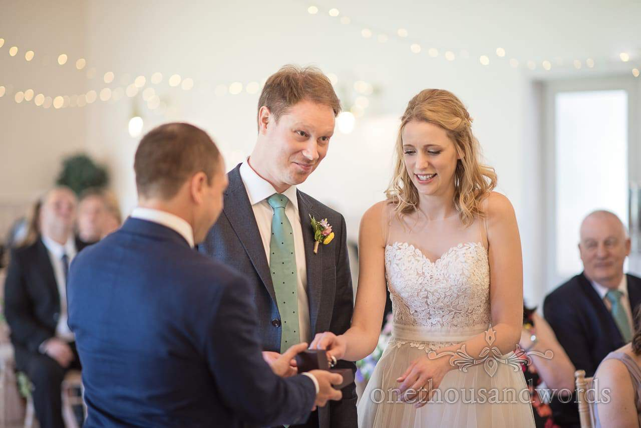 Groom pulls funny face as Best Man Hands over Wedding Rings to bride during wedding ceremony