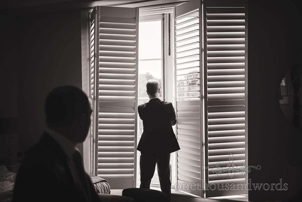 Documentary Black and White Groom Preparation Photograph with Slatted Windows Silhouette