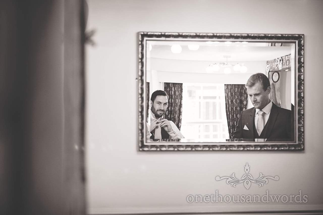 Black and white wedding photograph of groomsmen in mirror tying ties